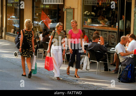 Three Swedish women with shopping bags walking past sidewalk restaurant on Stockholm street in summer - Stock Image