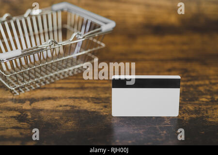 empty shopping basket with payment card on wooden table, concept of purchases and expenses - Stock Image