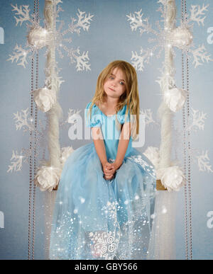 A princess little girl is sitting on a frozen swing against a blue winter backdrop with snowflakes for a fairy tale - Stock Image