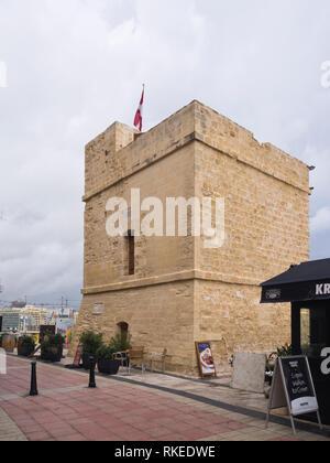 Saint Julian's Tower an old watchtower on the seaside promenade in Sliema Malta now in use as It-Torri Restaurant. - Stock Image