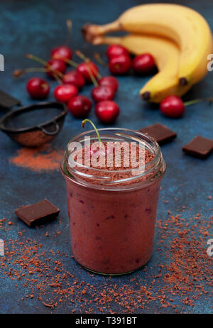cherry chocolate smoothie (black forest) in a jar on a dark blue background - Stock Image
