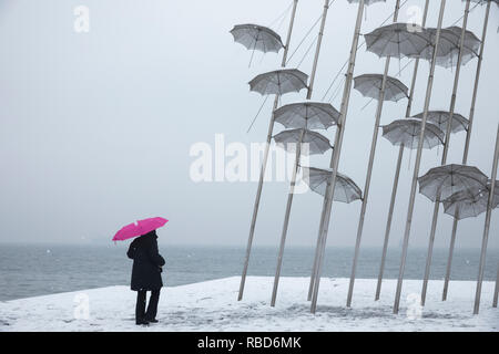 Thessaloniki, Greece. 09th Jan, 2019. A woman walks past Umbrellas sculpture by George Zongolopoulos artist during a heavy snowfall in Thessaloniki, Greece on January 9, 2019. Credit: Konstantinos Tsakalidis/Alamy Live News - Stock Image