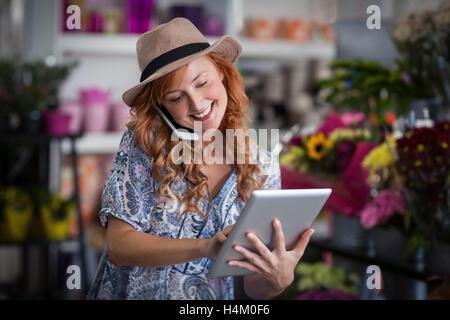Female florist talking on mobile phone while using digital tablet - Stock Image