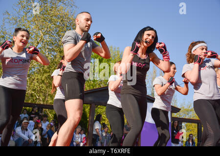 Nis, Serbia - April 20, 2019 Piloxing sport training group of young people on sunny spring day outdoor with happy instructor - Stock Image