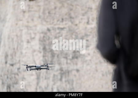 A man in the foreground is controlling a hovering drone just in front of him. Its been flown off a high cliff.on the English coast at studland, Dorset - Stock Image
