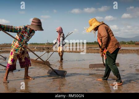 Cambodia, Kampot Province, Kampot, Tuek Chhou, Salt Fields, women preparing field for flooding with seawater - Stock Image