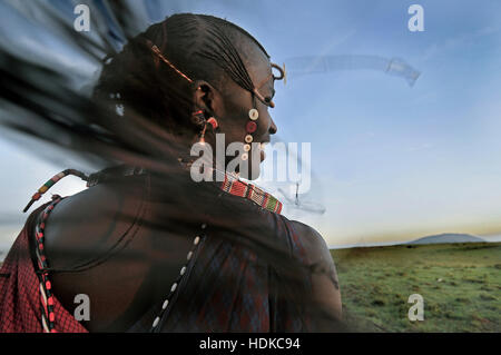 A Happy Maasai Warrior Tribesman with Traditional Braids Flying in the Wind - Stock Image