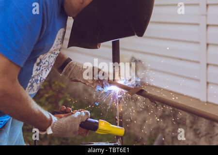 The process of welding metal rods male worker. Close-up - Stock Image