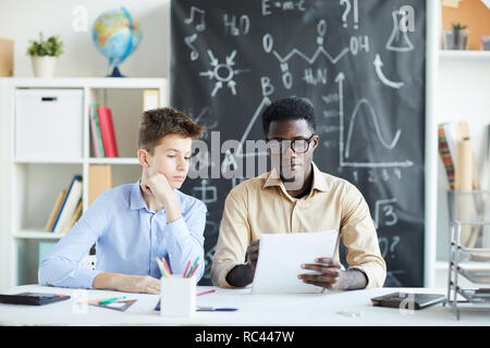 Serious teacher and schoolboy reading paper while sitting by desk and checking it after lesson - Stock Image