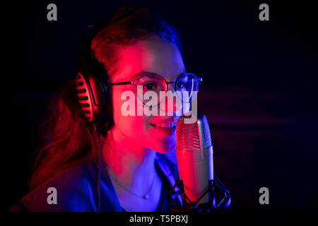 A young woman singing by the microphone in neon lighting - Stock Image