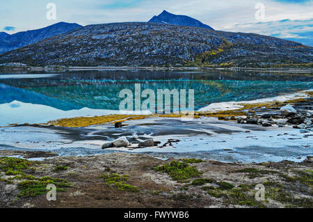 A bleak mountain is reflected in the calm water of fjord Ejfjord on Ofoten in northern Norway. - Stock Image