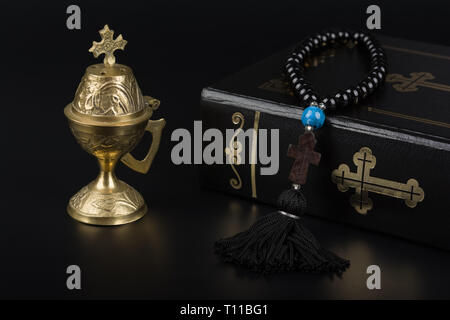 Closeup of Holy Bible, rosary beads with cross and incense burner on black background. Religion concept and faith. - Stock Image