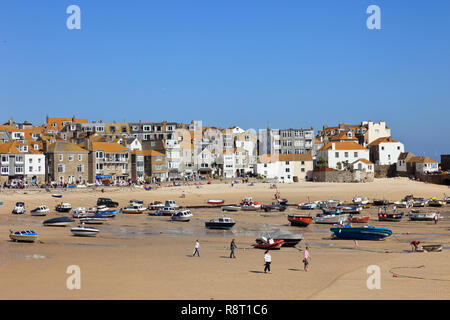 View of moored boats in the sandy harbour at low tide. St Ives, Cornwall, England, UK, Great Britain - Stock Image