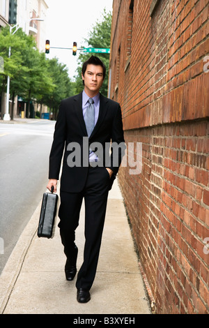 Asian business man walking down sidewalk in the city - Stock Image