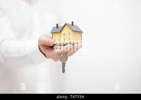 Small yellow house miniature with key in hand - Stock Image