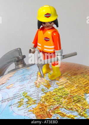Building worker on the globe as symbol for Europe in the change changes in the state landscape and or a new world order - Stock Image