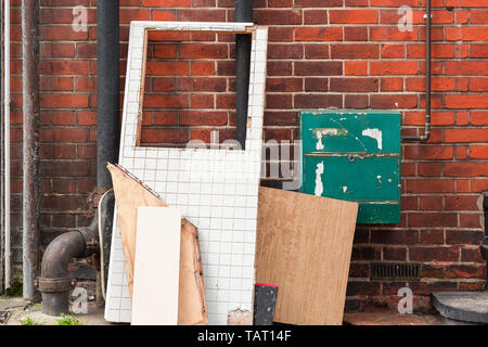 Large boards and waste items left against a brick wall at the corner of London street - Stock Image