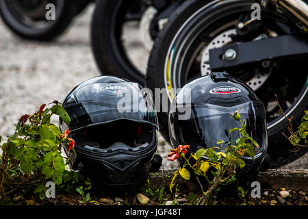 Two Caberg motorcycle helmets lying on a curb near motorcycles. - Stock Image