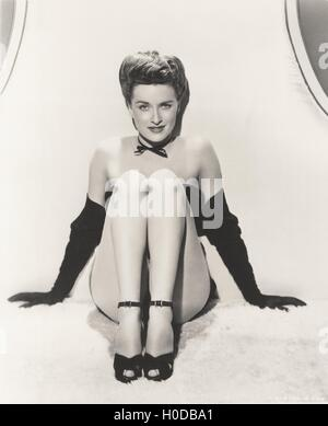 Showgirl posing in opera gloves and ankle strap shoes - Stock Image