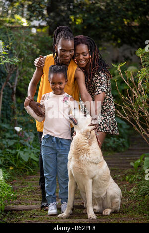 A family of women petting a dog - Stock Image