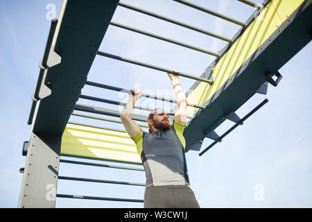 Serious determined bearded man in tight sportswear crossing monkey bars on outdoor training ground - Stock Image