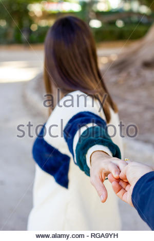 Girl looking in front pulls someone's hand while walking through an urban park - Stock Image