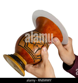 Hands tilting a gourd container (cuia) upside-down to form a mate wall, as part of the process of making the chimarrao, a Brazilian traditional drink, - Stock Image