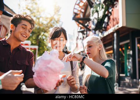 Group of friends eating cotton candy in amusement park. Young man and women sharing cotton candy floss at carnival. - Stock Image