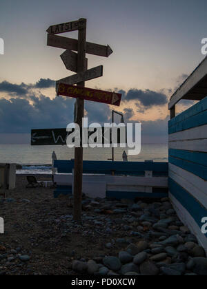 Signs pointing in different directions on a beach in Cyprus - Stock Image