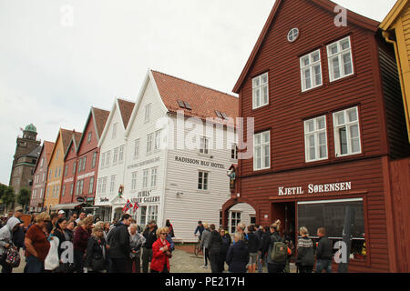Bergen, Norway - 9 August 2018: People seen walking by Bryggen (The Hanseatic Wharf) in the city of Bergen. The UNESCO World heritage site stems its roots from the Viking Age and it today home to many of the citoes restaurants, pubs, craft shops and museums. The city was for many years the centre of trade between Norway and the rest of Europe and is now usually the starting point to  expeditions into the country. Photo: David Mbiyu Credit: david mbiyu/Alamy Live News - Stock Image