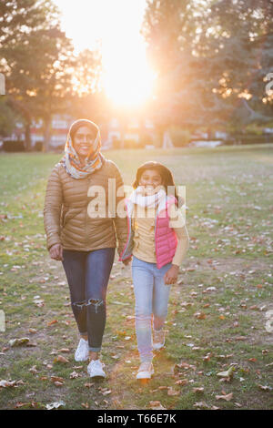 Portrait happy Muslim mother and daughter walking in sunny autumn park - Stock Image
