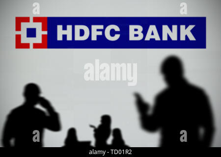 The HDFC Bank logo is seen on an LED screen in the background while a silhouetted person uses a smartphone in the foreground (Editorial use only) - Stock Image
