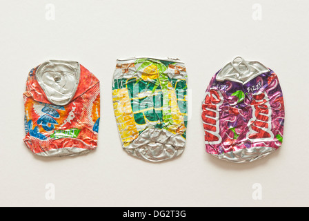 Three flattened soft drink cans on a plain background - Stock Image