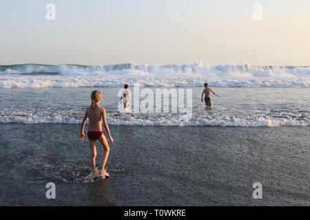 Three children playing in the surf during sunset on a beach in El Salvador - Stock Image