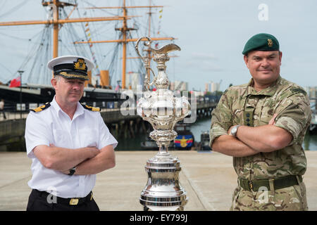 Portsmouth, UK. 23rd July 2015. A Navy officer and Royal Marine pose with the America's Cup in-front of HMS - Stock Image