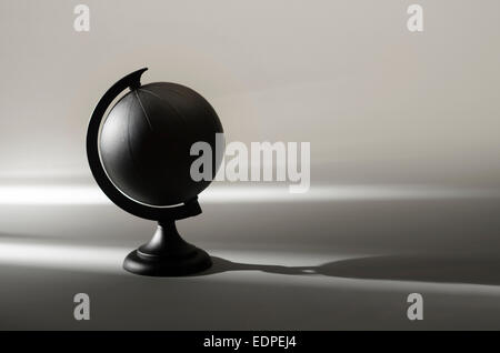 painted black globe earth planet in shadow - Stock Image