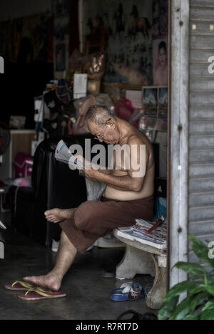 Thailand man reading the newspaper at home. Shirtless Asian man - Stock Image