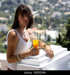 Windswept hair, young woman tourist holding glass of orange juice while enjoying the view from Mijas Pueblo, Costa - Stock Image