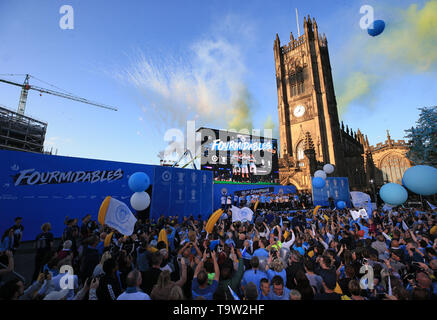 Fireworks go off as Manchester City celebrate onstage during the trophy parade in Manchester. - Stock Image