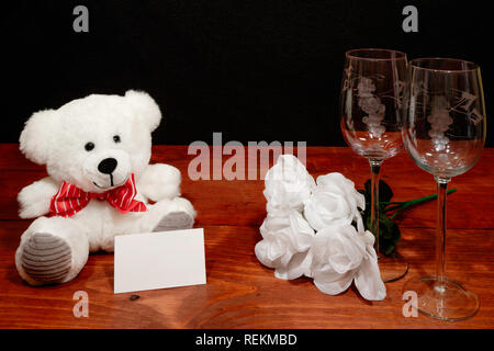 Beautiful etched wine glasses with white roses and white teddy bear and name tag on wooden table and dark background. Valentines, Mothers Day, Easter, - Stock Image