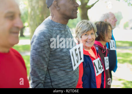 Portrait active senior woman at sports race starting line in park - Stock Image