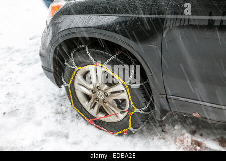 Snow chains installed on front wheel or tire of Honda passenger car on a snowy road while snowing. - Stock Image