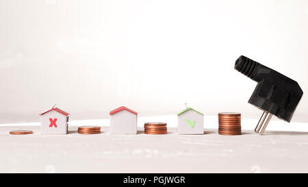 Save on electric bill concept: electric socket, paper houses and coin piles - Stock Image
