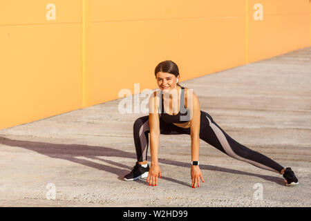 Young happy attractive woman wearing black sporwear practicing sport exercises in morning on street, stretching legs, toothy smile and looking at came - Stock Image