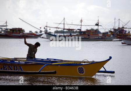 A Filipino starts his bangka boat in Mansalay Bay, Oriental Mindoro, Philippines. - Stock Image