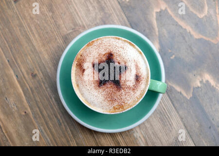 Cup of festive cappuccino coffee with a Christmas star design of chocolate sprinkled on frothy milk in a green cup and saucer UK  KATHY DEWITT - Stock Image