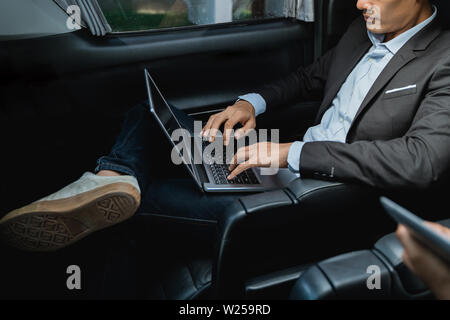 asian young businessman with tablet sitting on passenger seat of his luxury car - Stock Image