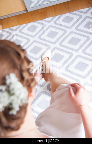 Bride,wedding,bridesmaid,groom,day,marriage,Forever,together,love,faithfulness,enters,in,the,hand,bruise,bracelet,sitting,leg,kn - Stock Image