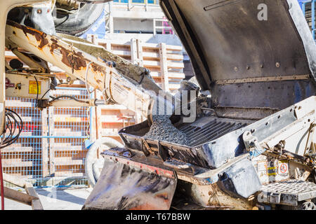 Cement being poured from a truck into a pumping apparatus. - Stock Image