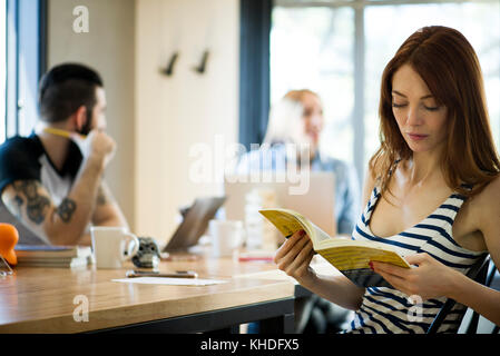 Woman reading book in shared office - Stock Image